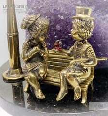 Bronze figures of cupid and sweethearts on a bench with a garnet heart on geodes amethyst agate background