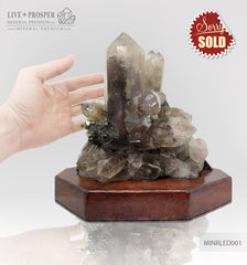 Collectible mineral specimen of Smoky quartz (Rauchtopaz) with Pyrite on a wooden stand
