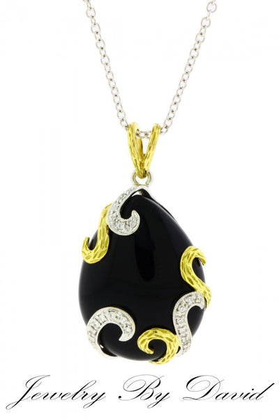 Designer brand pear shape black onyx diamond necklace in 18 karat 2 tone gold.