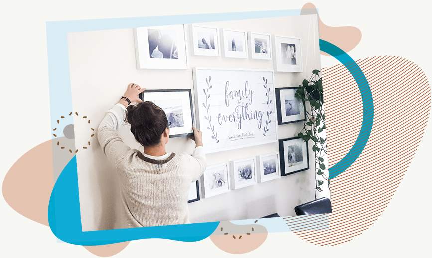 Anna adjusting a photo frame on her gallery wall