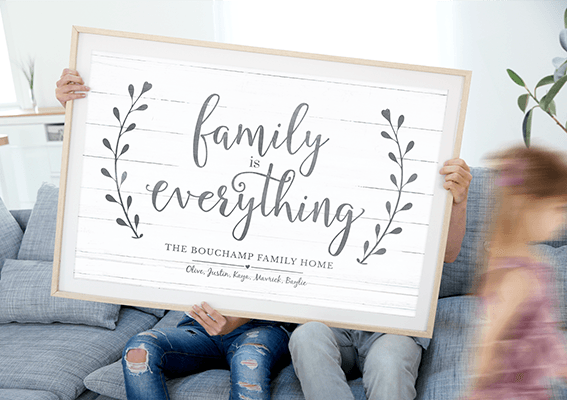 A Family holding their Family Is Everything personalized print in a beautiful home