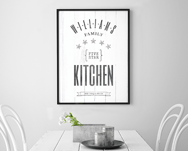 Five Star Kitchen personalized print framed in a black frame hanging over a dining table