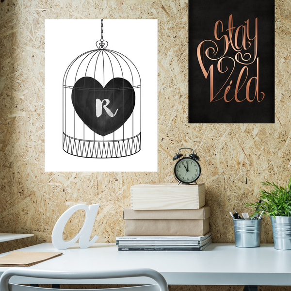 Bird cage with a heart and initial inside. Black and white print in a modern teenager's room