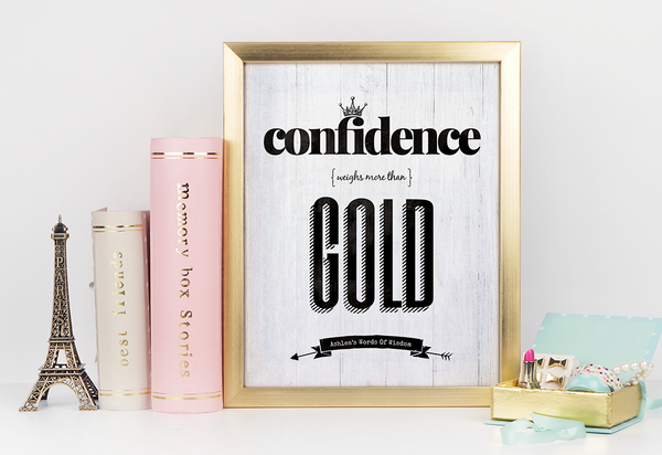 Desk with gold accents and a framed Confidence Weighs More Than Gold print