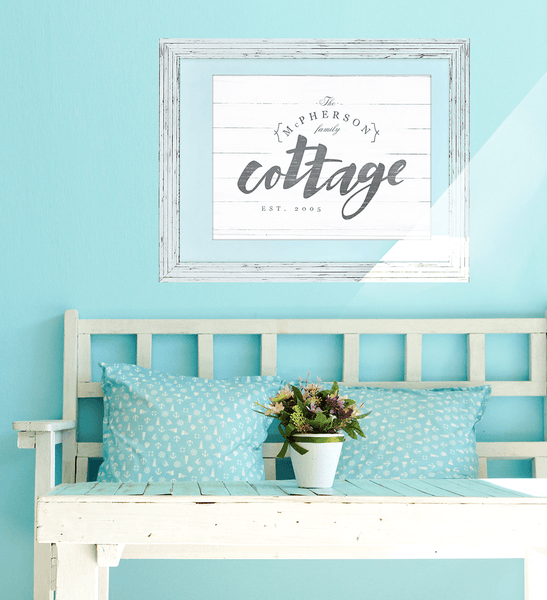 "white and blue cottage room with a personalized print ""Cottage"" hanging on the wall above a vintage bench."