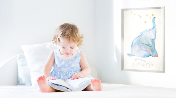 Baby girl sitting on bed reading. Good Luck print customized with her name is on the wall.