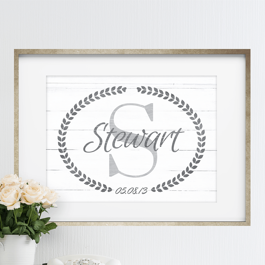 Framed Family Name print with a large initial and family name printed over it.