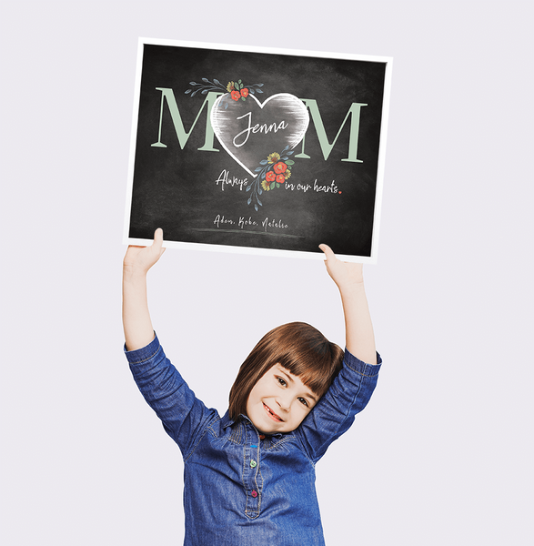 Little girl holding up Mom Heart personalized print for Mother's Day