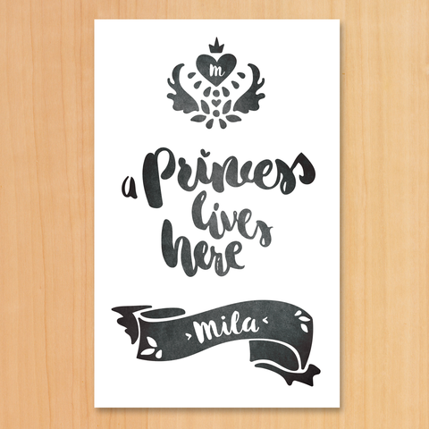 "A Black & White print with a royal crest and text ""A Princess Lives Here"". Set your girl's initial in the heart inside the crest and her name in the decorative banner below."