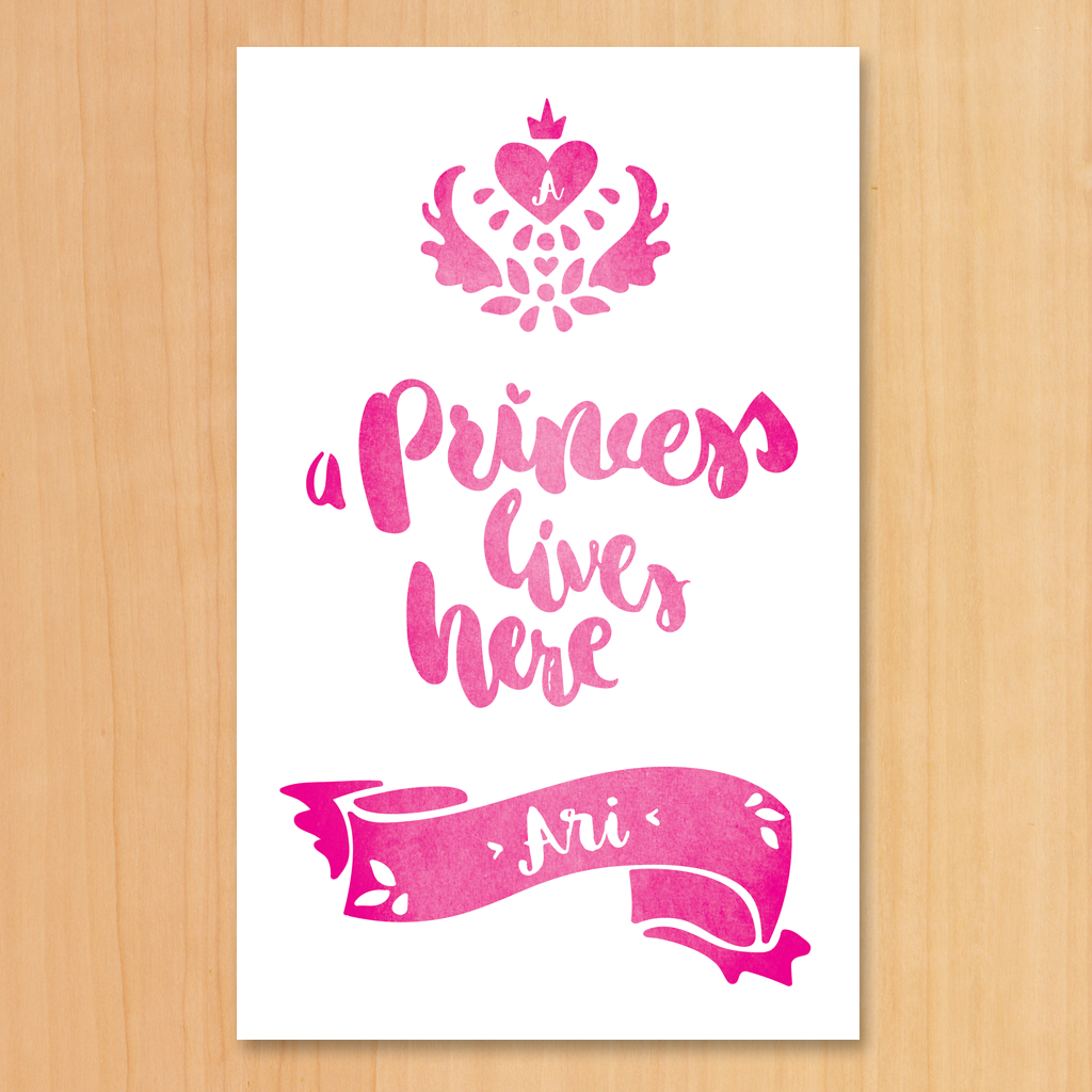 "A white and pink print with a royal crest and text ""A Princess Lives Here"". Set your girl's initial in the heart inside the crest and her name in the decorative banner below."