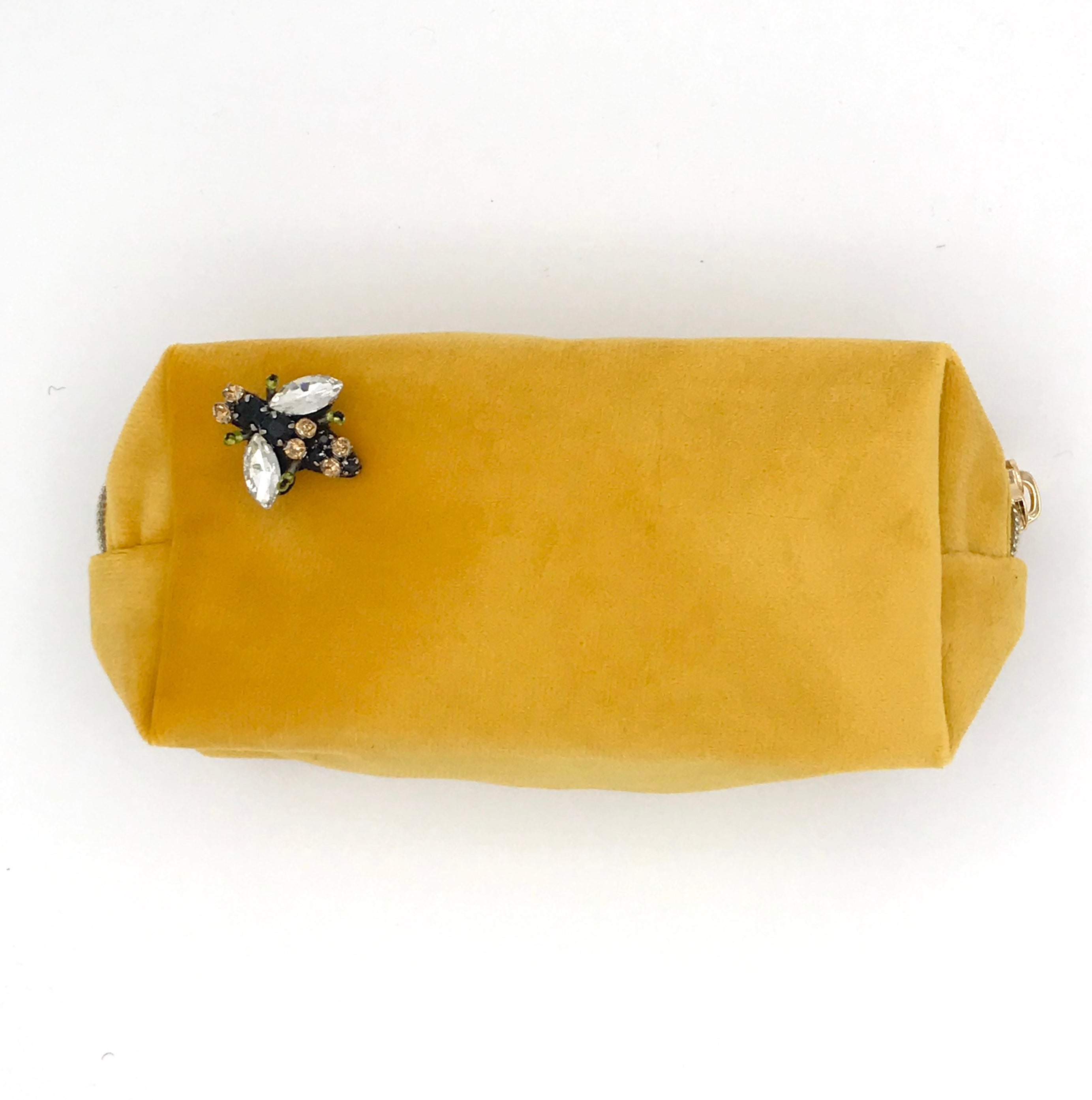 Velvet make-up bag in amber with a bumblebee pin
