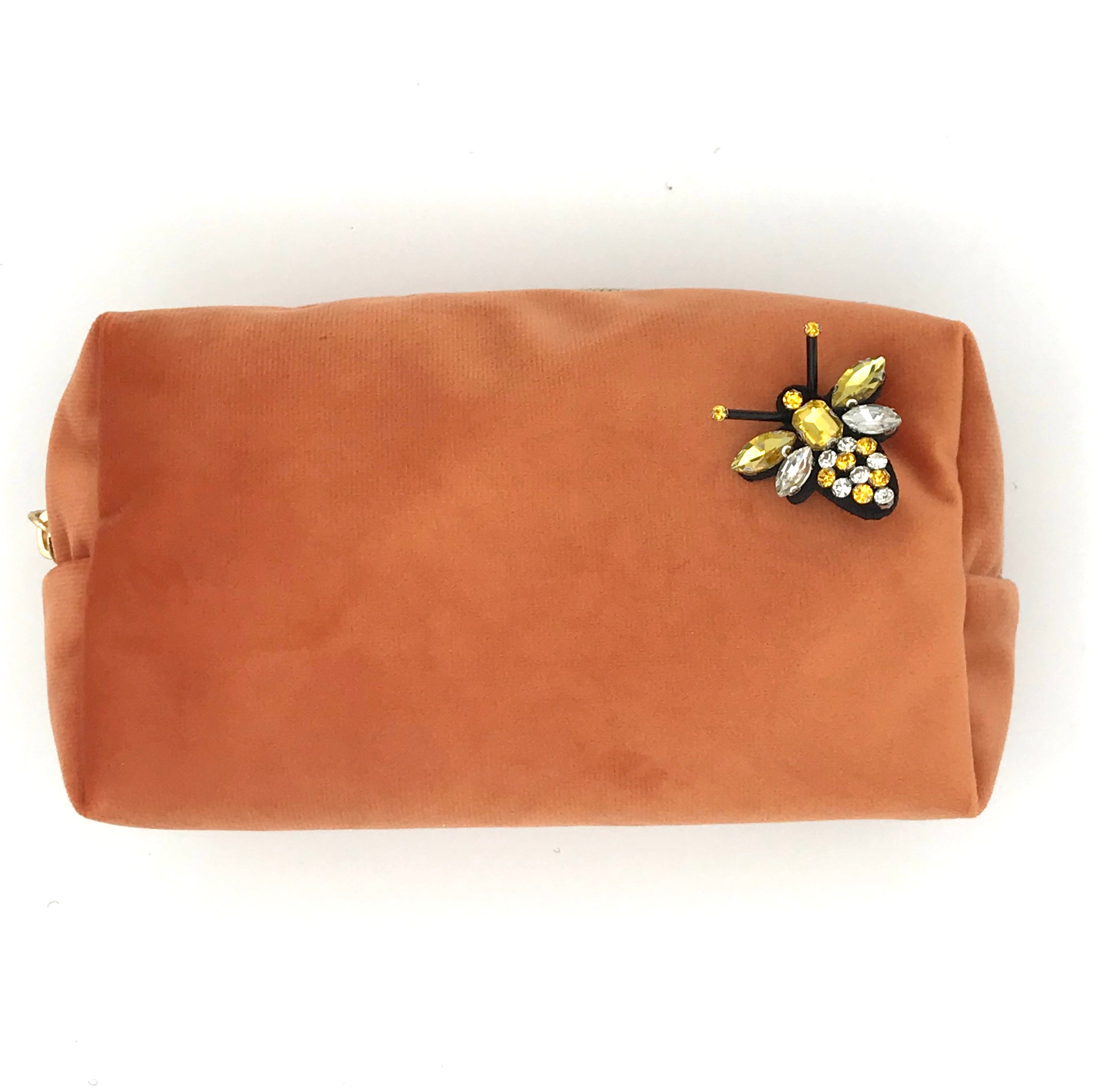 Velvet make-up bag in cantaloupe with a queen bee pin