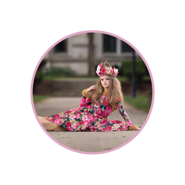 <alt>beautiful girl wearing spring flower dress and a custom handmade crown with pink and gold flowers by honeydrops designs sitting on the street</alt>