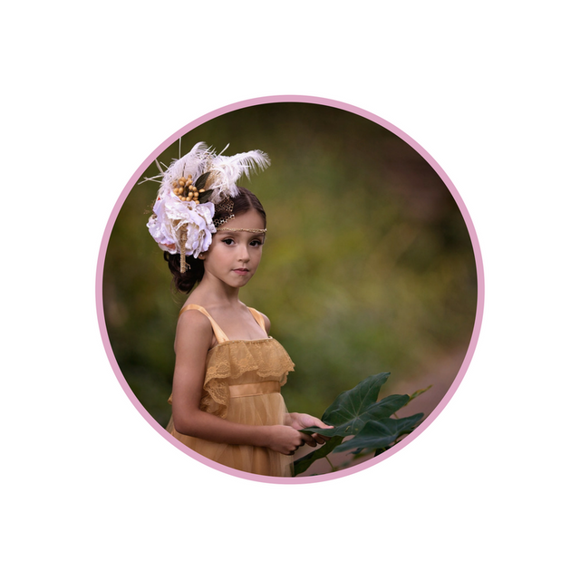 <alt>pretty model girl wearing couture handmade feather and flower headpiece by honeydrops designs holding flowers</alt>
