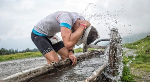 Alain Friedrich pours water over his head trying to stay cool at Swissman