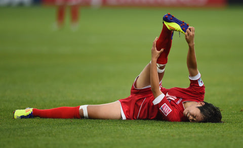 Footballer suffering with cramp, probably because he was dehydrated.
