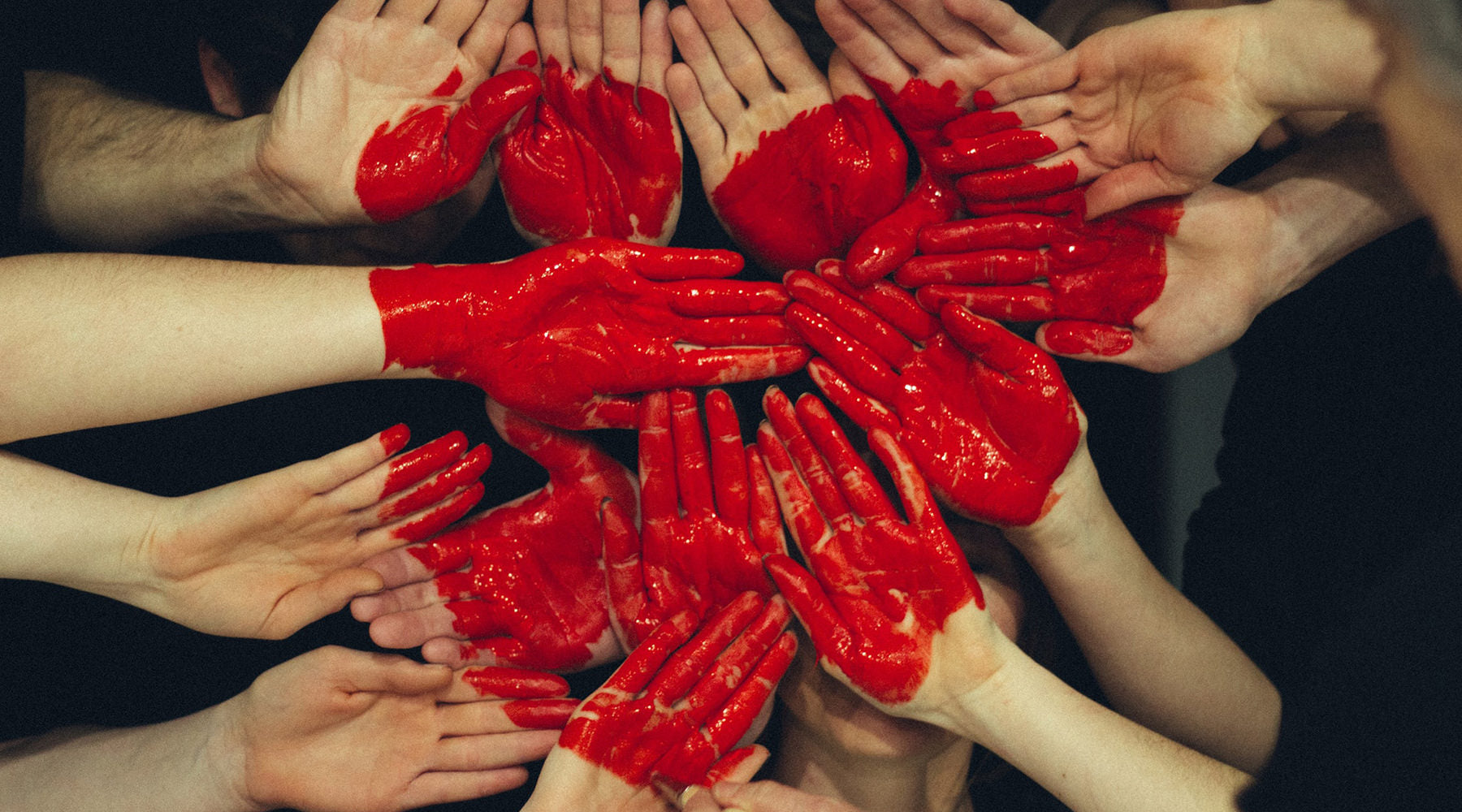 group of people with red heart painted on hands
