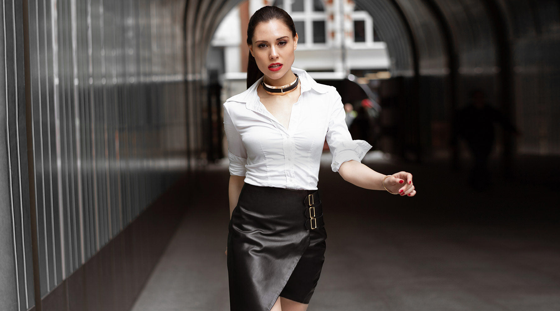 about the brand - woman walking towards the camera wearing mercer black leather skirt