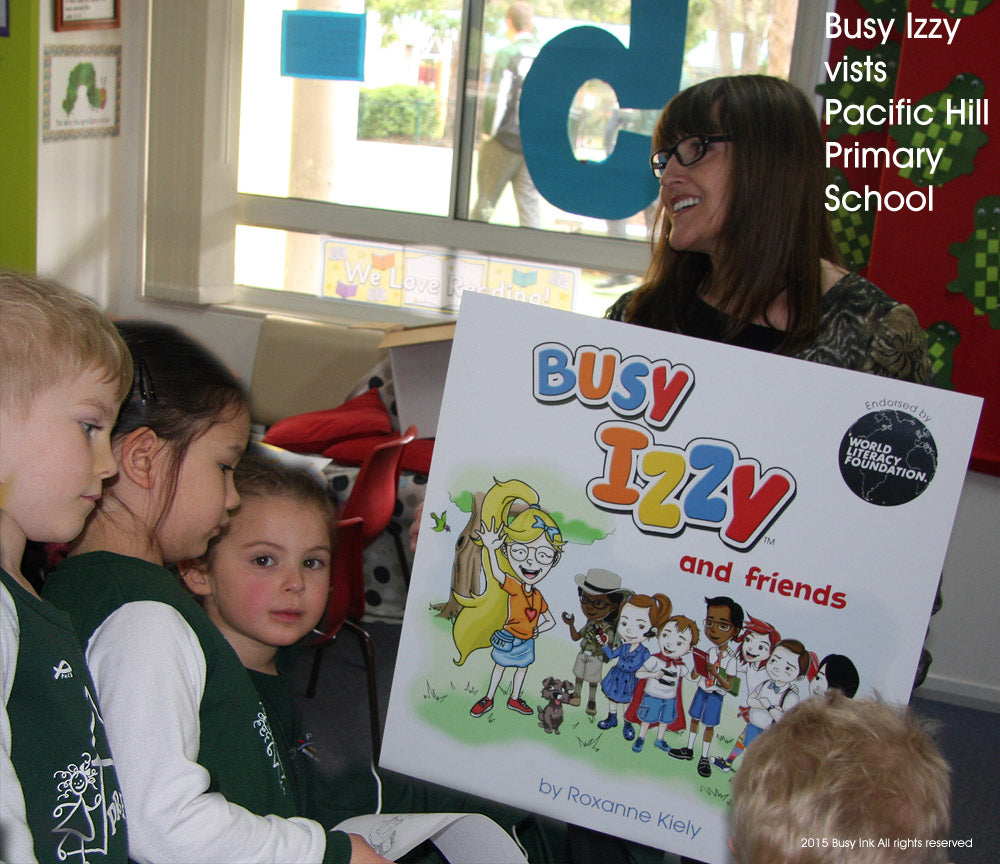 Roxanne shows the kids the cover of Busy Izzy book One