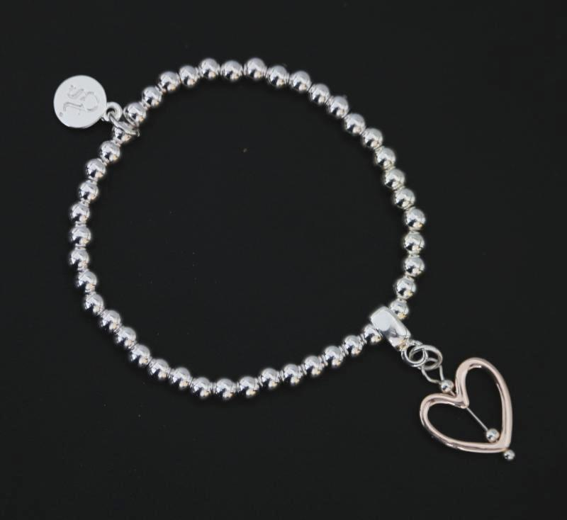 Stretchy silver beaded bracelet with rose gold open heart charm by Sarah Tempest.