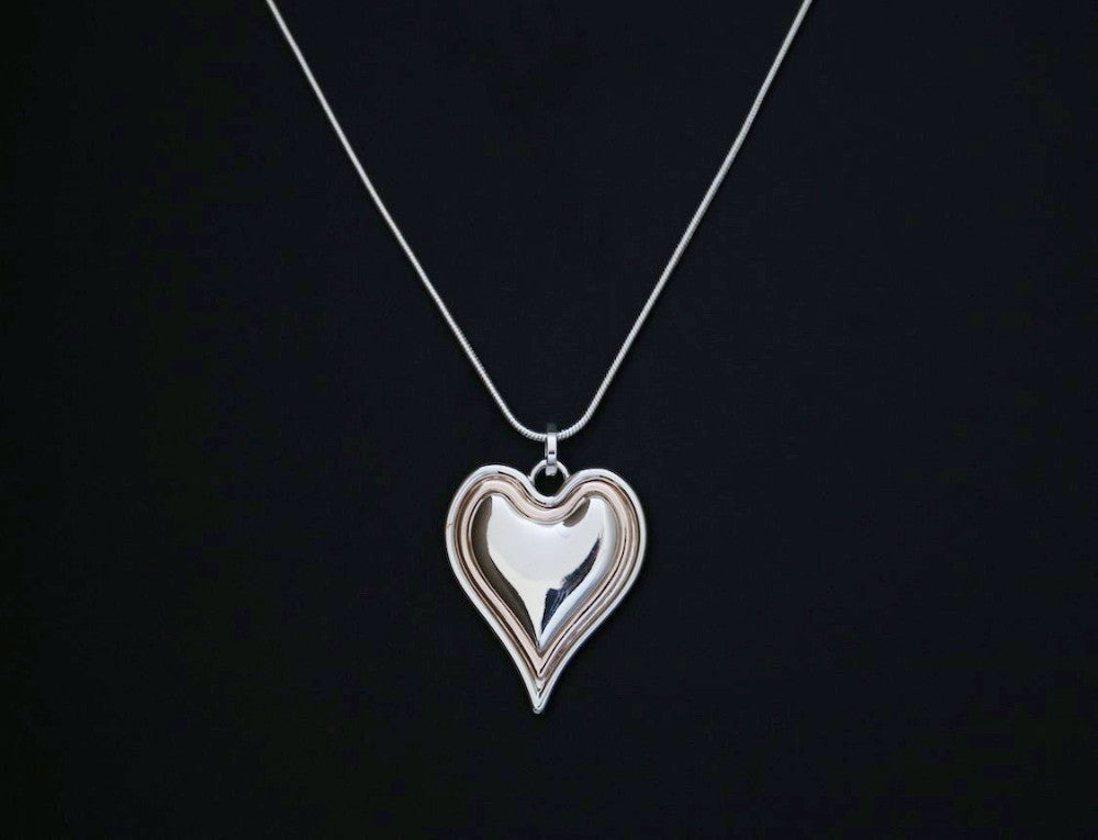 Heart shaped pendant long chain necklace in silver and rose gold designed and made by Sarah Tempest.