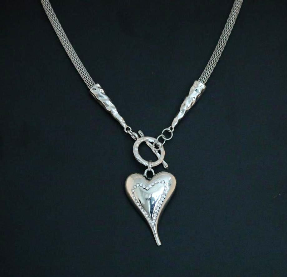Highly polished encrusted metal heart pendant on a mesh chain with T-bar fastener.