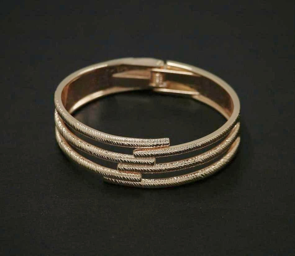 Spring loaded bangle in rose-gold colour with textured finish.