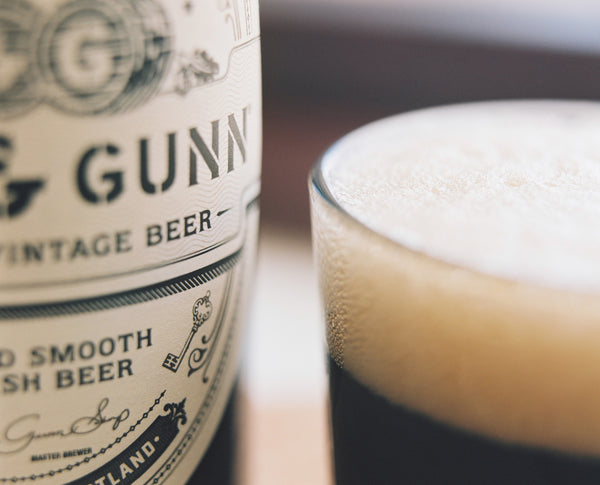 Close up photograph of Innis & Gunn Vintage beer bottle and glass of poured beer with a thick rich head