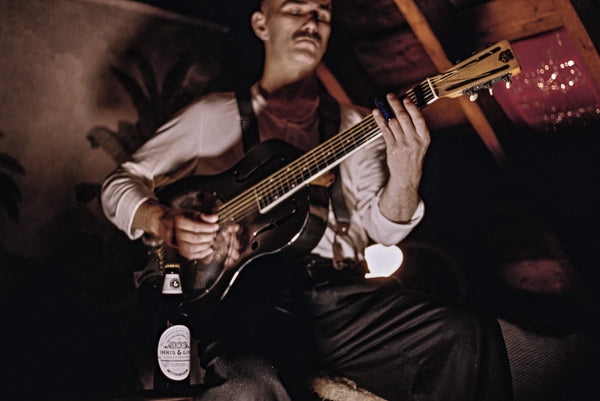 Photograph of a man playing steel guitar with a bottle of Innis & Gunn Vintage beer in the foreground.