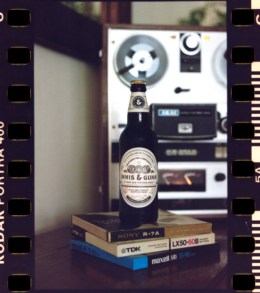 Innis & Gunn Vintage beer bottle with a Reel to Reel tape deck in the background