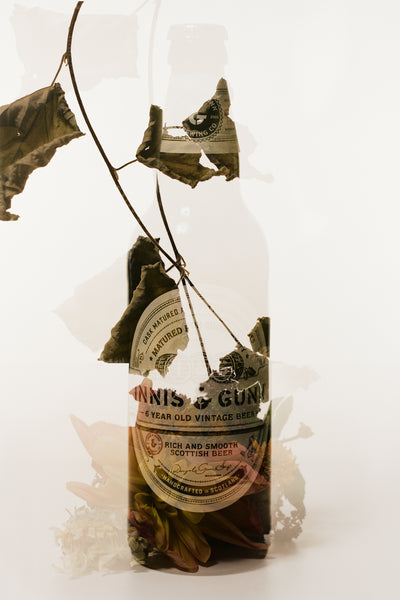 Double Exposure photograph of Innis & Gunn Vintage beer bottle and dried leaves