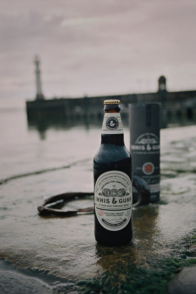 Photograph of Innis & Gunn Vintage beer bottle and carton on a wet harbour wall