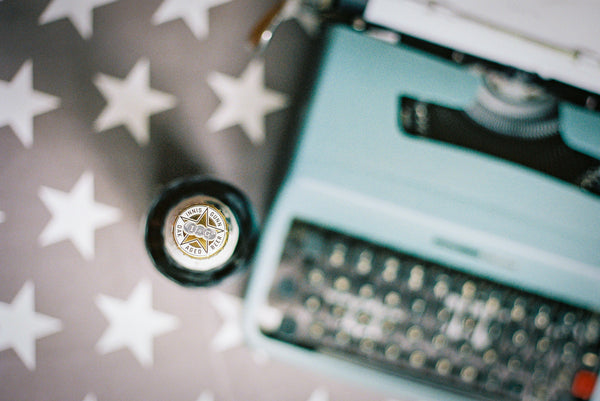 Photograph from above showing a vintage typewriter and bottle of Innis & Gunn Vintage beer