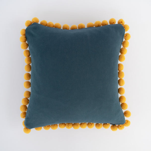 Reverse of the ivy pom pom cushion by Hannah Knapton showing blue/grey hand dyed reverse and mustard pom poms