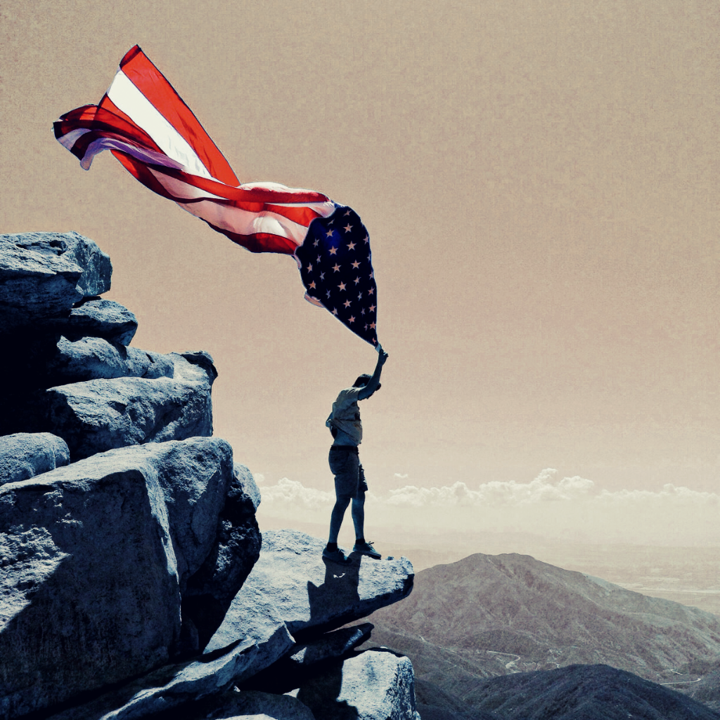 Man on a cliff holding American flag