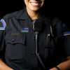 female officer smiling and wearing a police lapel pin