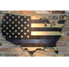 thin blue line flag on wood hanging on brick wall with light shining
