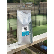Raw Bean Unpacked Classic house blend part of the Waitrose Unpacked trial, pack shot on wooden ledge with Padel court in the background