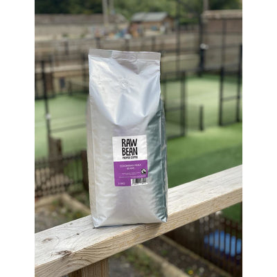 Raw Bean Unpacked Colombian Huila part of the Waitrose Unpacked trial, pack shot on wooden ledge with Padel court in the background