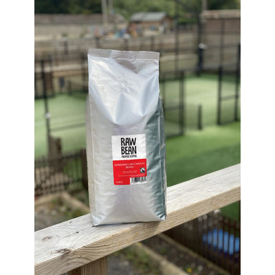 Raw Bean Unpacked Honduran Cafe Capucas part of the Waitrose Unpacked trial, pack shot on wooden ledge with Padel court in the background
