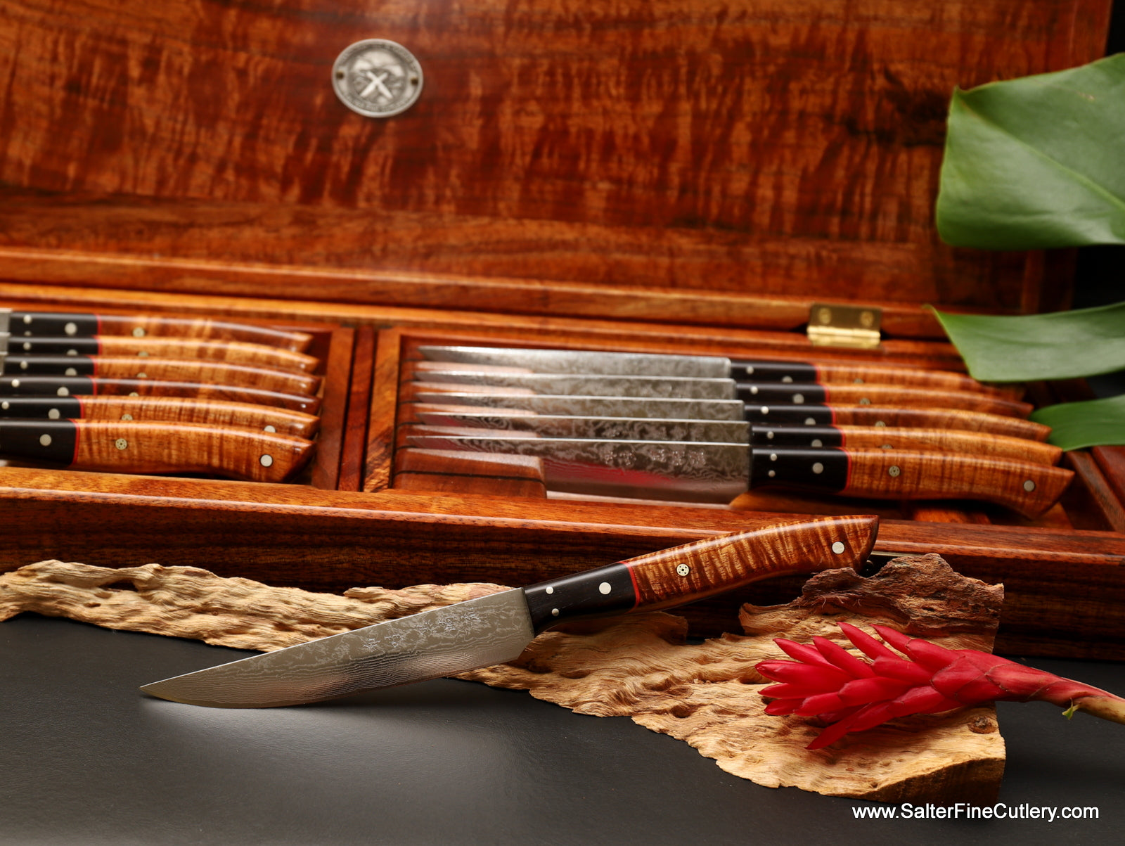 Featuring VG10 individually hand-forged damascus blades, this 12-piece luxury steak knife set in display presentation box has handles of curly Hawaiian koa wood with ebony bolsters from Salter Fine Cutlery