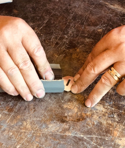 Each knife individually made by hand like the hand-sanding process of a metal handle fitting seen here by Salter Fine Cutlery