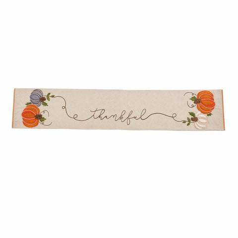 "Pumpkins on each end of a beige table runner with ""thanful"" embroidered in the middle"