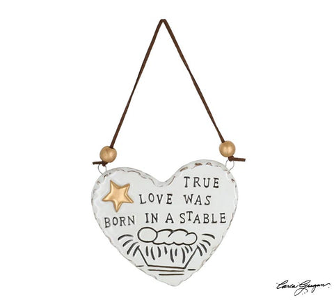White heart with a manger, baby, message, and star.