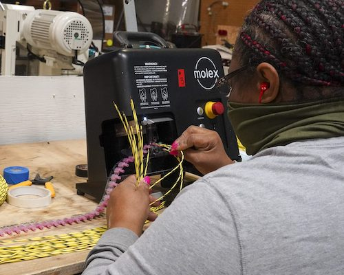 Photo courtesy Equalizer Systems. An employee working in the Harness Shop.