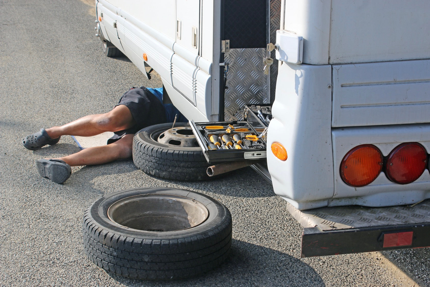 Man under recreational vehicle changing tire