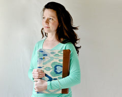 Brunette woman holding stunning ikat laptop case in her arms