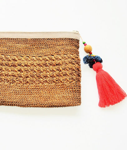 brown raffia boho clutch with oversized orange tassel and leather trim