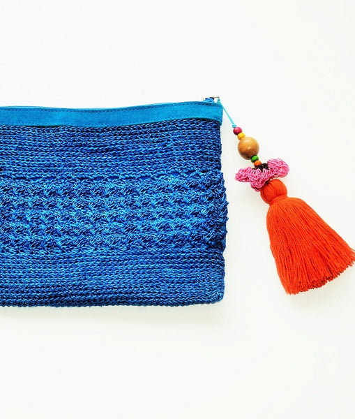 blue raffia boho clutch with oversized orange tassel and leather trim
