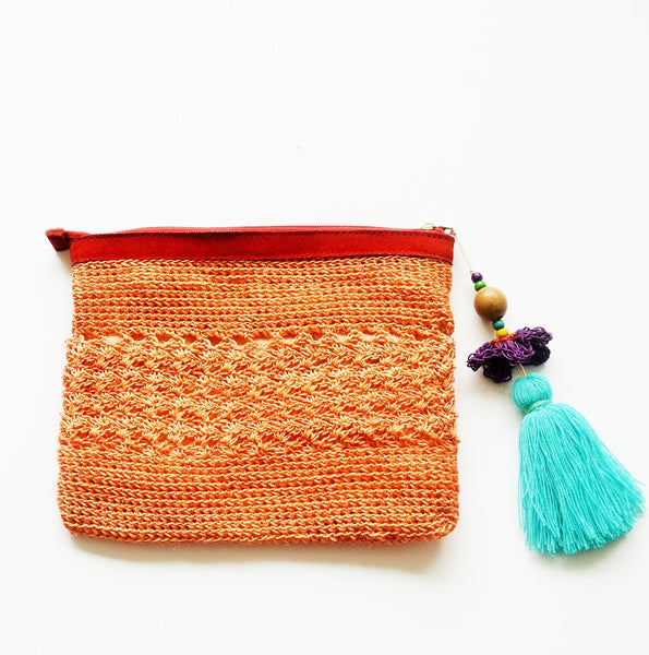peach raffia boho clutch with oversized aqua tassel and leather trims